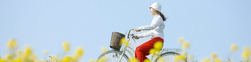 A young woman rides a bicycle through a summer field