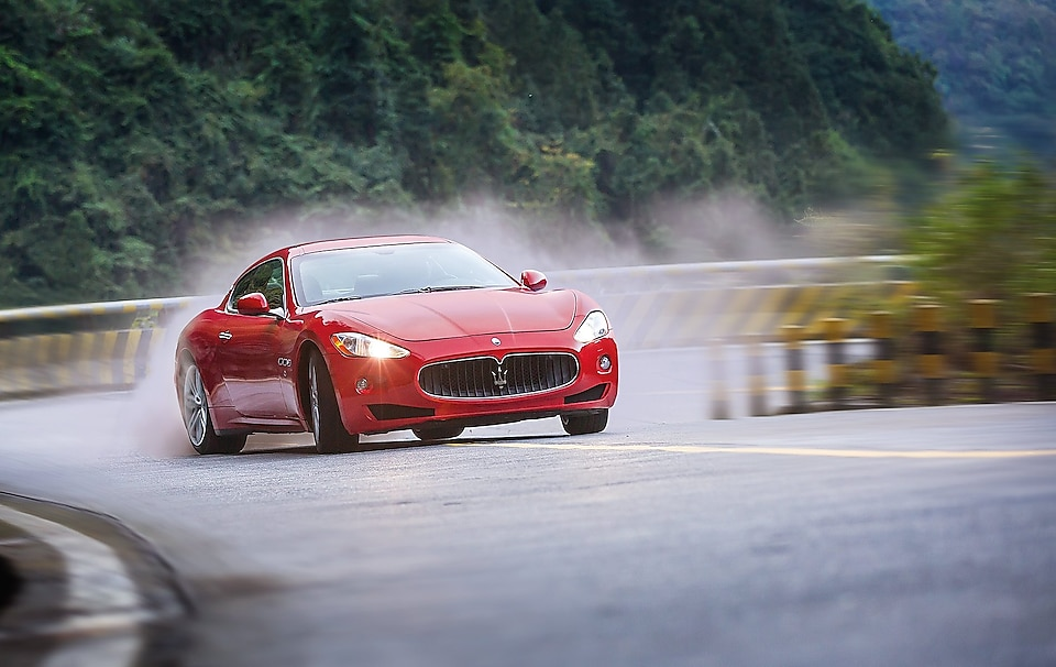 Red Maserati climbing up mountain road